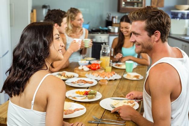 Casal sorridente, olhando um ao outro enquanto tomando café da manhã