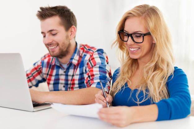 Casal sorridente pagando contas em casa