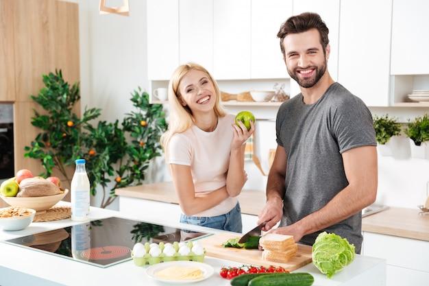 Casal sorridente, passar algum tempo juntos na cozinha