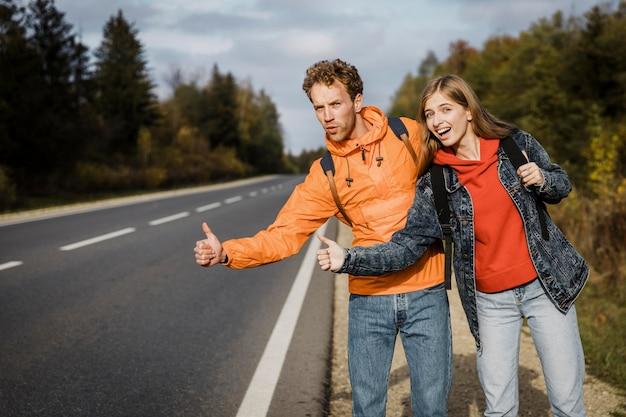 Casal sorridente pedindo carona durante uma viagem