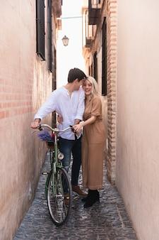 Casal sorridente posando ao ar livre com bicicleta