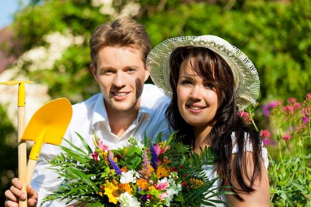 Casal sorridente posando com ferramentas de jardinagem e flores