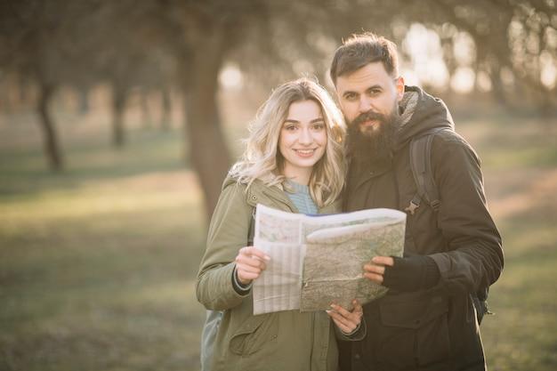 Casal sorridente posando com mapa