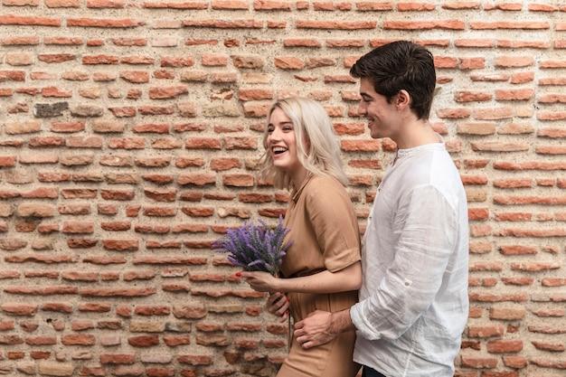Casal sorridente posando enquanto segura o buquê de flores de lavanda
