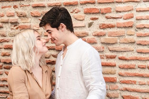 Casal sorridente posando enquanto vai para um beijo