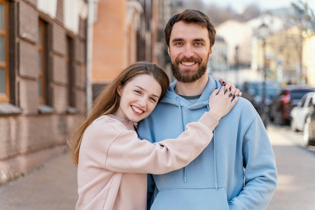 Casal sorridente posando juntos ao ar livre na cidade