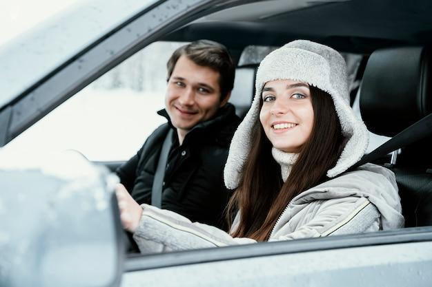 Casal sorridente posando juntos no carro durante uma viagem
