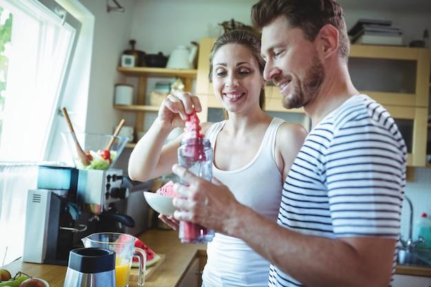 Casal sorridente preparando smoothie de melancia na cozinha