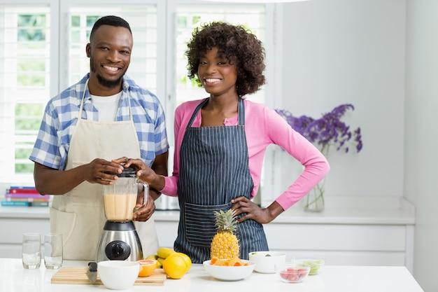Casal sorridente preparando smoothie de morango na cozinha em casa