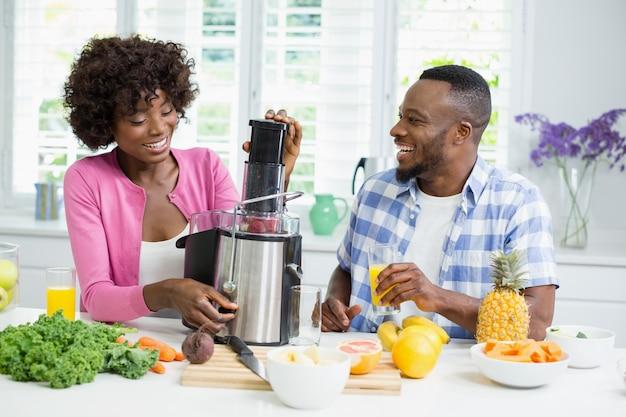 Casal sorridente preparando smoothie de morango na cozinha