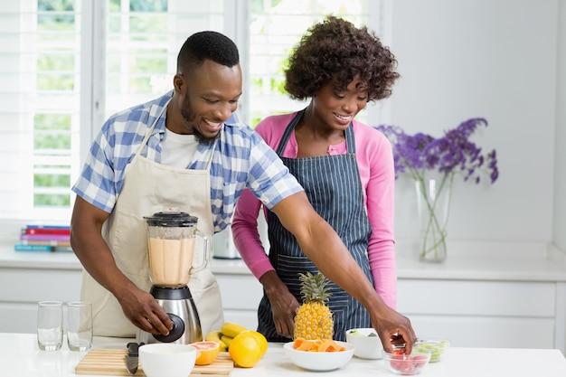 Casal sorridente preparando suco de frutas na cozinha