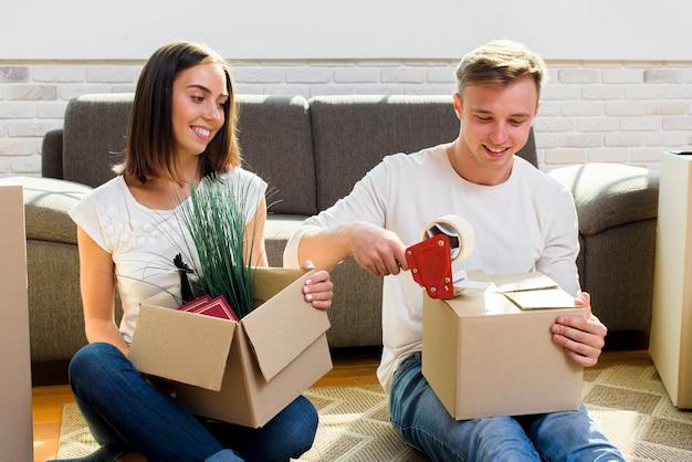 Casal sorridente pulando caixas de papelão