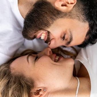 Casal sorridente quase se beijando em casa