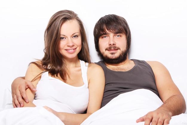 Casal sorridente relaxa na cama