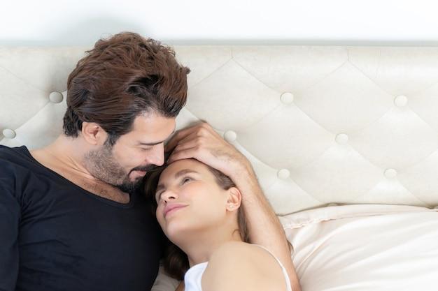 Casal sorridente relaxando e casais se abraçando na cama