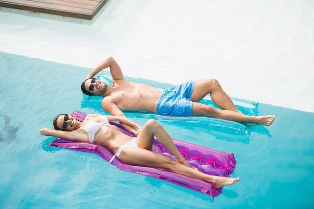 Casal sorridente relaxante na balsa inflável