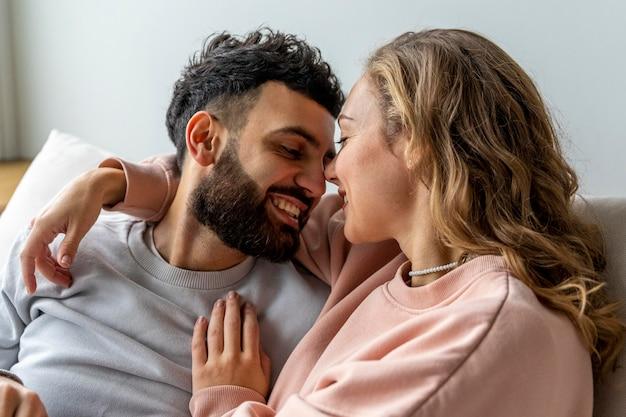 Casal sorridente romântico relaxando em casa