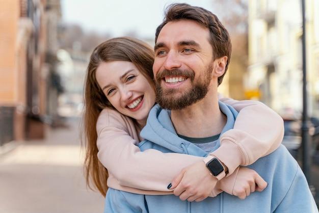 Casal sorridente se abraçando ao ar livre na cidade