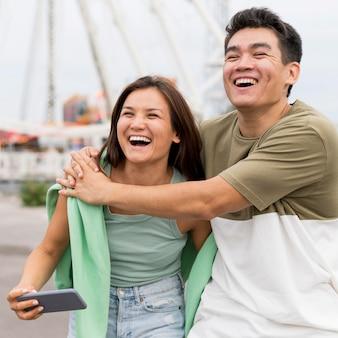 Casal sorridente se abraçando ao ar livre
