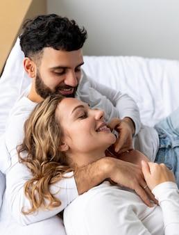 Casal sorridente se abraçando na cama em casa