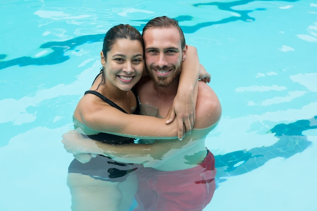 Casal sorridente se abraçando na piscina