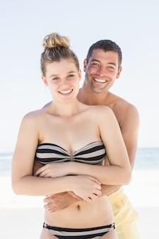 Casal sorridente se abraçando na praia