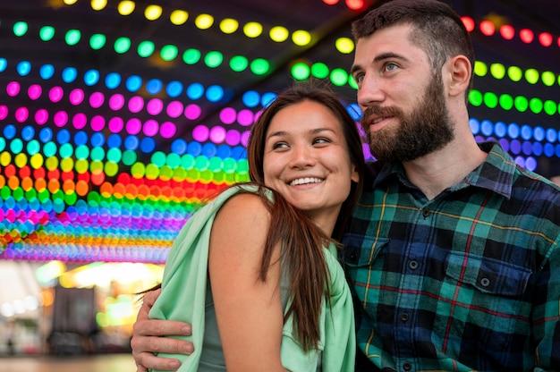 Casal sorridente se abraçando no parque de diversões