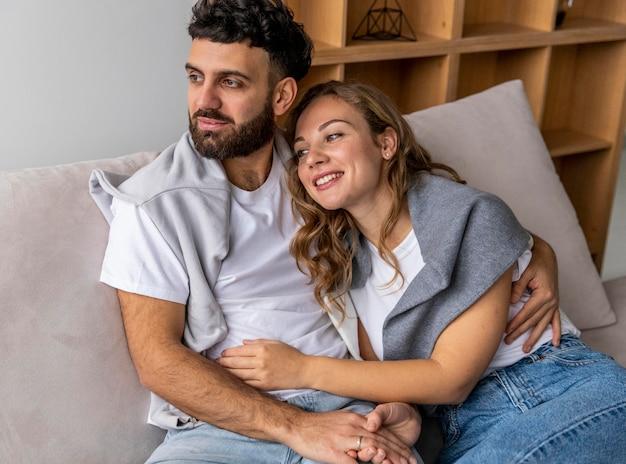 Casal sorridente se abraçando no sofá em casa