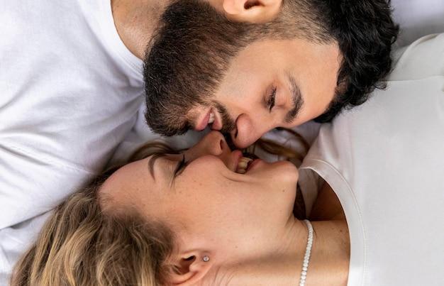 Casal sorridente se beijando na cama em casa