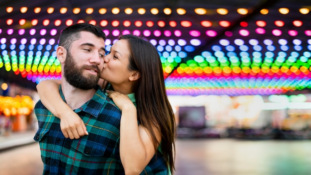 Casal sorridente se beijando no parque de diversões