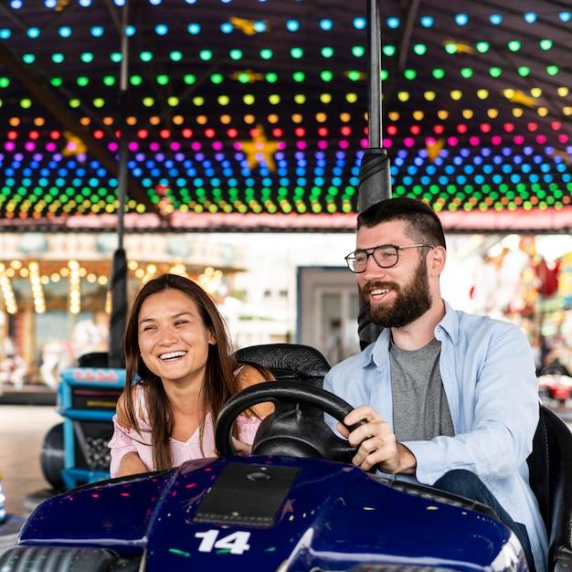 Casal sorridente se divertindo com carrinhos de choque