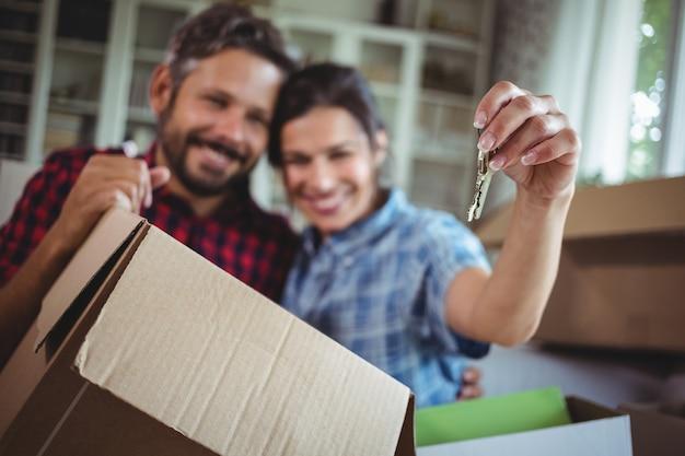 Casal sorridente segurando as chaves em sua nova casa
