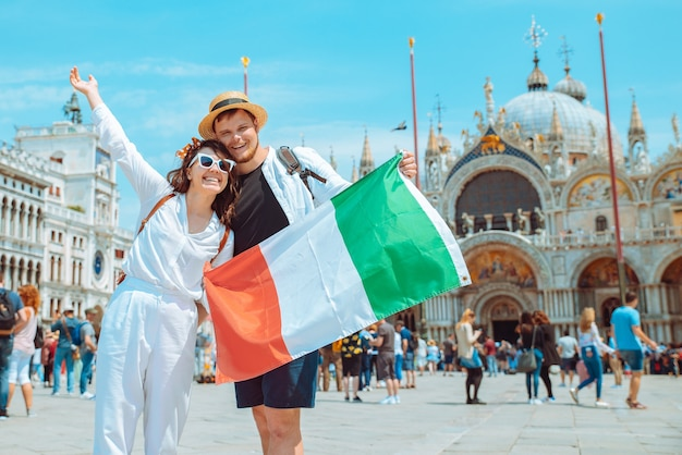 Casal sorridente segurando bandeira italiana na praça central de veneza, san marco, cópia espaço