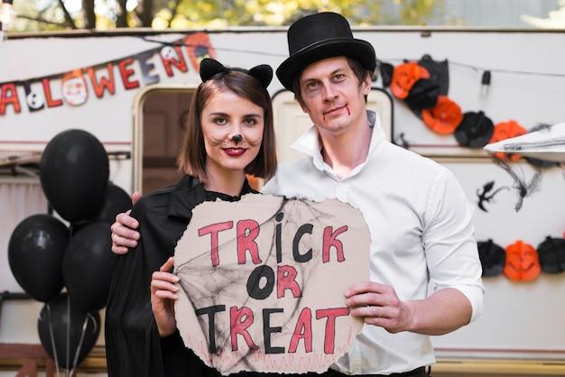 Casal sorridente segurando cartaz de halloween