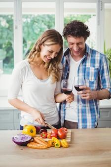 Casal sorridente segurando copos de vinho na cozinha