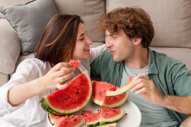 Casal sorridente segurando fatias de melancia