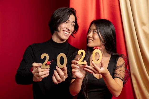 Casal sorridente segurando figuras de sinal e rato de ano novo