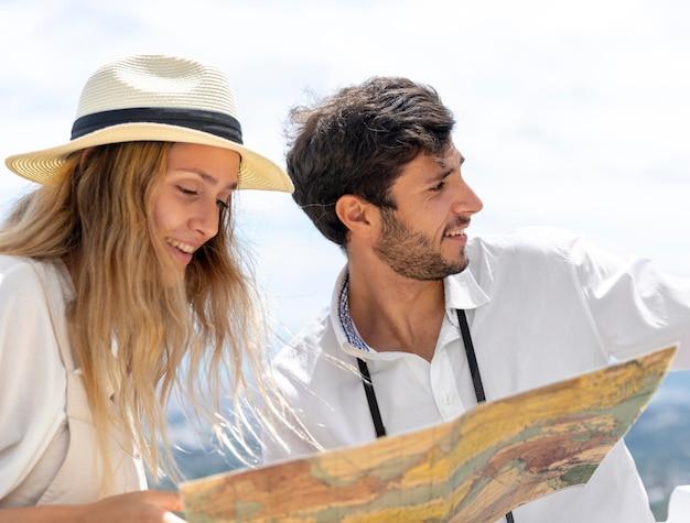 Casal sorridente segurando mapa médio