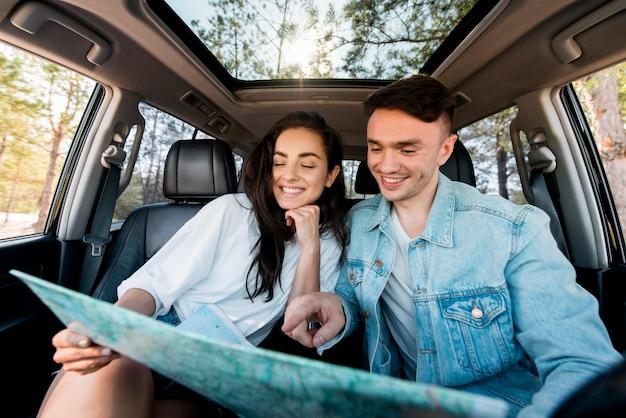 Casal sorridente segurando o mapa de frente