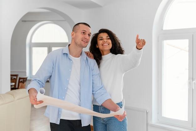 Casal sorridente segurando plantas de casa