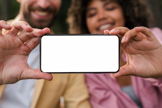 Casal sorridente segurando smartphone enquanto acampa ao ar livre
