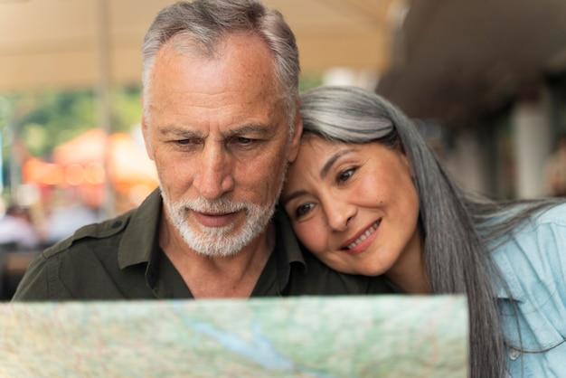 Casal sorridente segurando um mapa