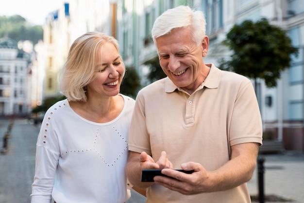 Casal sorridente sênior ao ar livre na cidade com smartphone