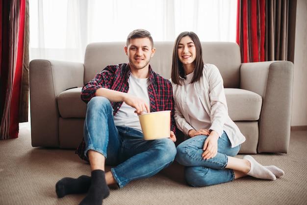 Casal sorridente, sentado no chão, encostado no sofá, assistindo tv com pipoca em casa, homem com controle remoto na mão
