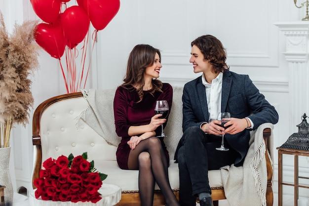 Casal sorridente, sentado no sofá, bebendo vinho e olhando um para o outro