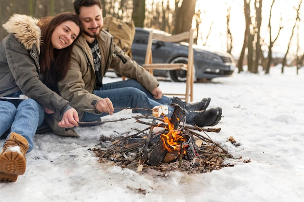 Casal sorridente sentado perto do fogo