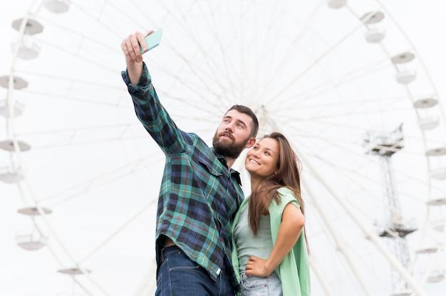 Casal sorridente tirando selfie ao ar livre