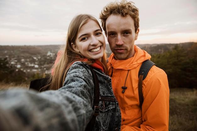 Casal sorridente tirando uma selfie durante uma viagem juntos