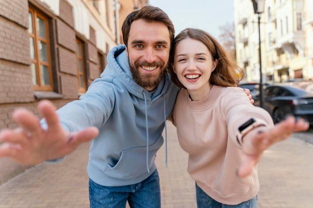 Casal sorridente tirando uma selfie e fingindo estender a mão