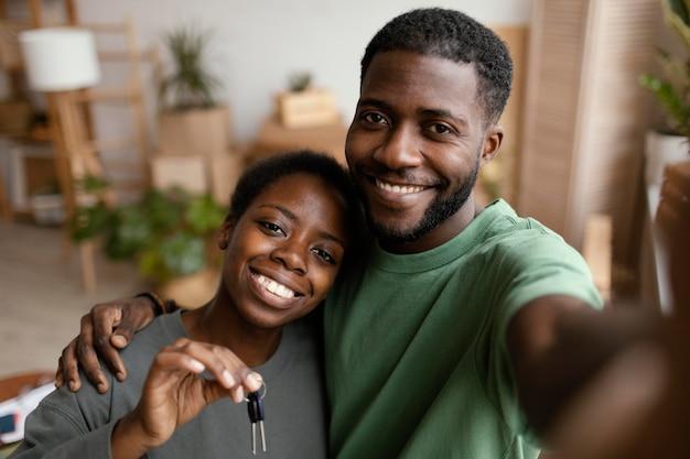 Casal sorridente tirando uma selfie em sua nova casa